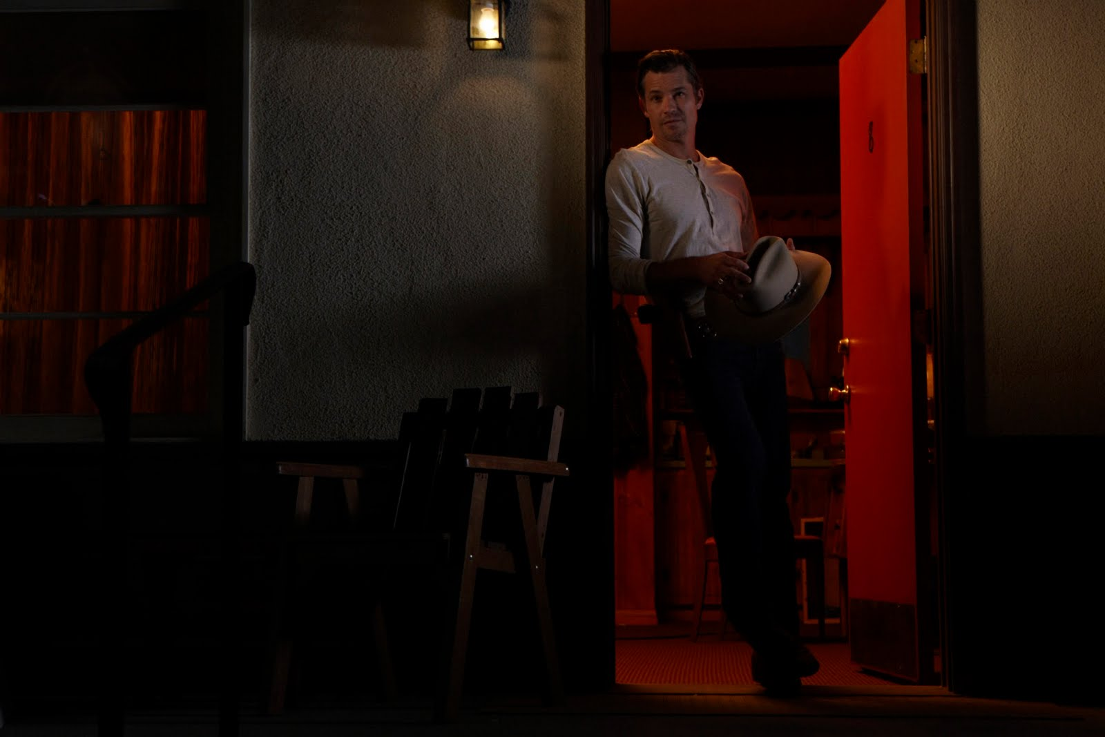 raylan in doorway hat in hand