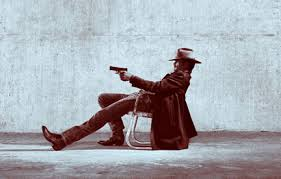 raylan in chair gun pointed boots
